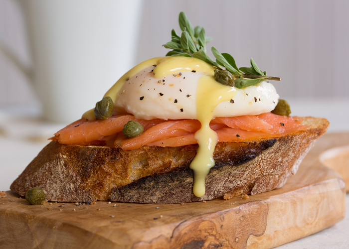 Eggs benedict on crusty bread with salmon, capers and a creamy hollandaise