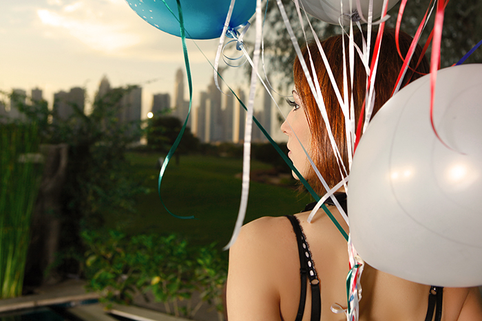 Birthday image of young woman with party baloons