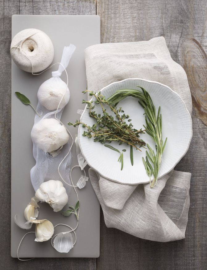 Garlic, rosemary & thyme on grey wood.